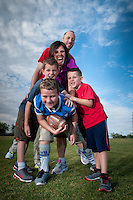 DOG PILE! Stacy and Rich Johnson and their  boys,  Cooper, 7, left, Travis, 6, right and Daniel 9 at Paseo Vista Park in Chandler.