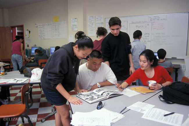Albany CA High school students looking at old year books while preparing their new one in journalism class
