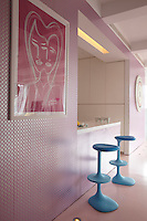 Metallic patterned wallpaper covers the wall between the living area and the kitchen