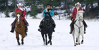 Trio of cowgirls riding their horses across a snowy field