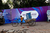 A young boy plays with a tricycle carrier outside the Commonwealth Games hoarding that hides his slums in New Delhi, India.