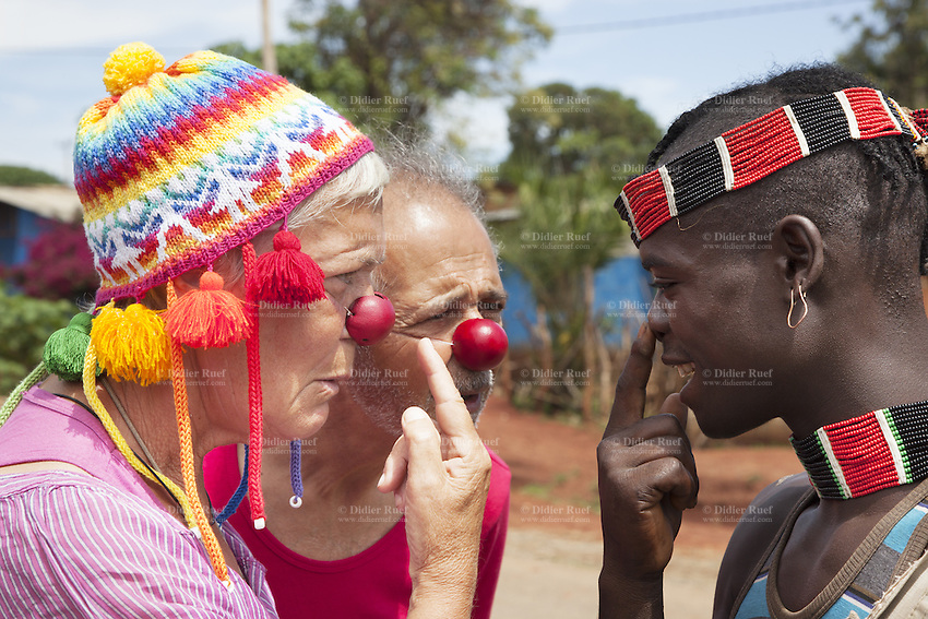 """Ethiopia. Southern Nations, Nationalities, and Peoples' Region. Omo Valley. Keyafer. Soizic Triennot (L) and Jean Marc Chetrit (R) wear both a glossy red plastic clown nose and talk to a man from the Bena tribe. Marc Vella is a french musician and a nomadic pianist. Over the last 25 years he has travelled with his Grand Piano in around forty countries to celebrate humanity. Creator of """"La Caravane amoureuse"""" (The Caravan of Love) he takes people with him to say """"I love you"""" to others and """"lovingly conquered"""" their hearts and souls. Banna, Bana, and Benna are other spellings for the Bena people which are mainly agricultural people. The Omo Valley, situated in Africa's Great Rift Valley, is home to an estimated 200,000 indigenous peoples who have lived there for millennia. Southern Nations, Nationalities, and Peoples' Region (often abbreviated as SNNPR) is one of the nine ethnic divisions of Ethiopia 12.11.15 © 2015 Didier Ruef"""