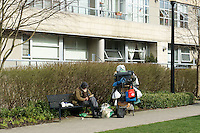 Homeless man sitting on a bench reading a book, Vancouver, British Columbia, Canada