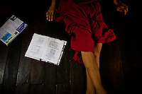 A monks reads a newspaper along with his Buddhist passages.