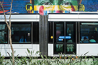 Rio de Janeiro Light Rail ( Portuguese - VLT do Rio de Janeiro or VLT Carioca ), a light rail system opened in June 2016 ahead of the 2016 Olympic Games passes in front of Eduardo Kobra s Mural named Native people from the 5 continents ( Povos nativos dos 5 continentes ) at Boulevard do Porto in Rio de Janeiro port surrounding area, Brazil, part of the Porto Maravilha Project ( Marvelous Port Program ), a revitalization project of the city Port Zone. Kobra is a Brazilian street artist notable for painting large murals, usually depicting portraits with a technique of repeating squares and triangles, utilizing bright colors and bold lines while staying true to a kaleidoscope theme.