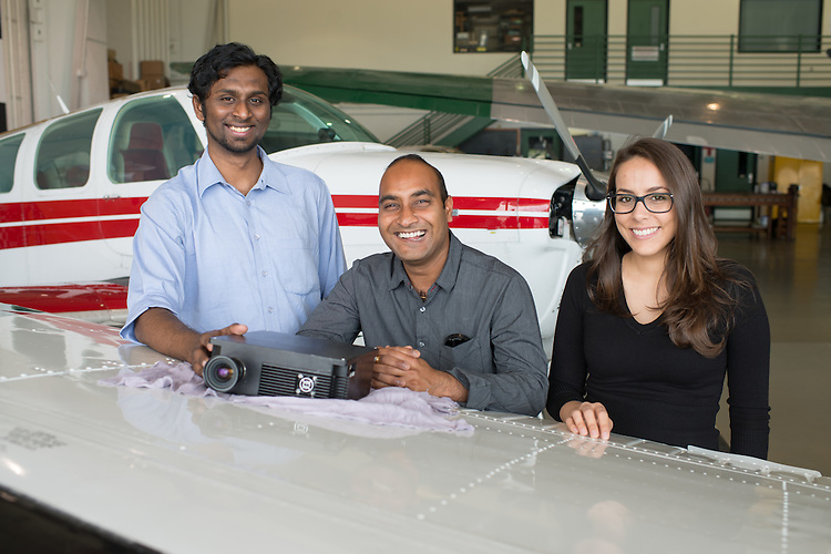 (Left to Right) Nikhil Dhinagar, Saikat Ghosh and Caroline Santolaya stand next to a prototype sensor that they are using collect pollution datavia airplane above shale drilling sites. Photo by Ben Siegel