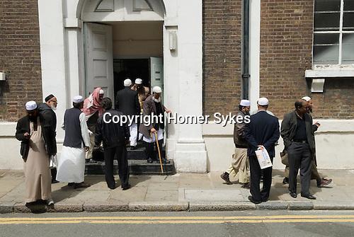 Men leaving Friday Prayers Jamme Masjid Mosque Brick Lane London E1.