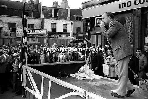 Hoxton, London. 1976<br /> John Tyndall leader of the National Front, a raciest anti-immigration party, drums up support from an almost exclusive male audience from the back of a lorry, decked out in Union Jack flags at the Saturday Hoxton Street market on November 27th. By the 1979 general election, the NF was able to field 303 candidates, polling over 191,000 but failed to win a seat in parliament.