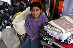 A  young girl poses for a portrait  at the Plaza de Ponchos  Market, Otavalo, Ecuador.