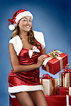 Smiling beautiful young woman with Christmas gifts. Isolated on blue background
