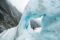 Lonely hiker in big blue ice cave on Franz Josef Glacier in moody weather, Westland Tai Poutini National Park, UNESCO World Heritage Area, West Coast, New Zealand, NZ