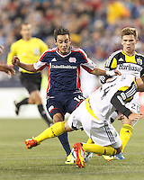 New England Revolution midfielder Diego Fagundez (14) about to endure a slide tackle. In a Major League Soccer (MLS) match, the New England Revolution (blue) defeated Columbus Crew (white), 3-2, at Gillette Stadium on October 19, 2013.