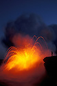 Man watching lava explode as flow from Pu'u O'o eruption hits ocean; Hawaii Volcanoes National Park.
