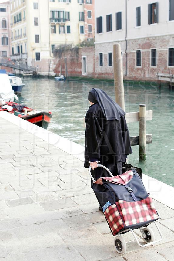 Una suora cammina col suo carrello della spesa lungo un canale di Venezia.<br /> A nun walks with her shopping trolley along a canal in Venice.<br /> UPDATE IMAGES PRESS/Riccardo De Luca