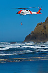 A U.S. Coast Guard Helicopter launches a rescue swimmer into the surf at Cape Disappointment in Washington State near the mouth of the Columbia River.