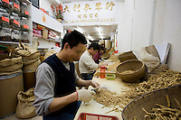 Man prepares Korean Red Ginseng roots for sale at Tai Lai Ginseng Hong shop, Wing Lok Street, Sheung Wan, China