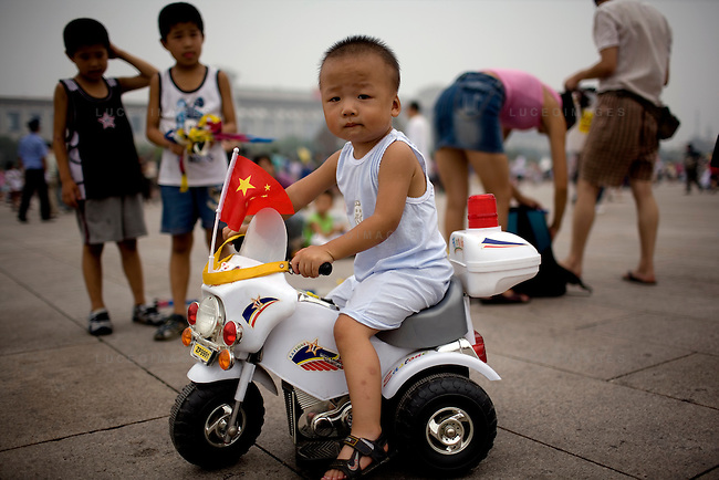 A boy rides his toy police motorcycle in Tian'anmen Square in Beijing, China on Sunday, August 10, 2008.  Kevin German