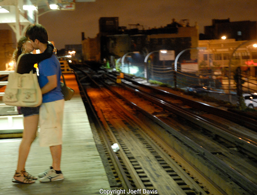 A couple kisses while waiting for the El late night in Chicago, Illinois.