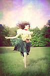 Prancing girl in a field with windblown hair and a floral dress