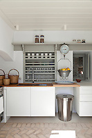 The contemporary white kitchen has a bespoke shelving unit picked out in a contrasting pale grey