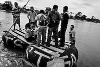 A makeshift inner tube raft, carrying immigrants from Central America, leaves the shore of the Suchiate river in Tecún Umán, Guatemala, heading to Mexico, 22 May 2011. Having no migration or commercial controls, the Suchiate river serves as an illegal crossing point between the southern Mexican state of Chiapas and Guatemala. Every day, hundreds of people from both countries, crossing the river on the unstable rafts called ?camaras?, smuggle soft drinks, toilet papers, fruits, vegetables and other supplies. The river crossing is also widely used by the Central America immigrants heading to the north, to the United States, in the search of better life.