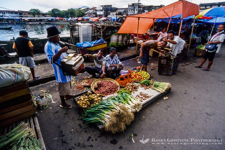 Indonesia, Sulawesi, Manado. Salesmen offering their goods on the market in Manado harbour.