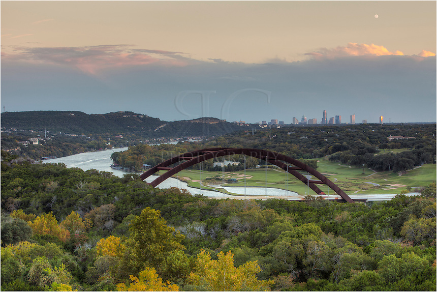 In the early evening, the moon rises over the Austin Skyline. In the foreground is the 360 bridge, also known around here as Pennybacker bridge. the Texas version of the Colorado River flows under the bridge and down into Ladybird Lake. In the Austin cityscape, you can see the Austonian, the tallest building in Austin, along with the 360 Condos building. On the far left of the Austin skyline is the Texas State Capitol.