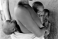 """Mozambique. Province of Tete. Manje is a small village in the bush. A mother and her three children are waiting oustside a hut for a medical consultation. The village can only be reached by plane. Because of the war between the Government and the rebel of the Frelimo party, the roads are either mined or too dangerous to travel on.The plane is part of the  """"Flying Doctors"""" programm ran by the non governmental organisation (ngo) Médecins Sans Frontières (MSF) of Belgium.   © 1992 Didier Ruef"""