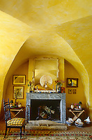 Under the vaulted ceiling of the living room a matching pair of folding stools flanks the grey marble fireplace