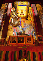 A giant statue of Maitreya Buddha (future Buddha) towers over portraits of the Panchen Lama inside Tashilhunpo monastary, Tibet