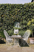The paved patio area is furnished with a pair of wrought iron chairs and a simple table topped with a Dutch birdhouse