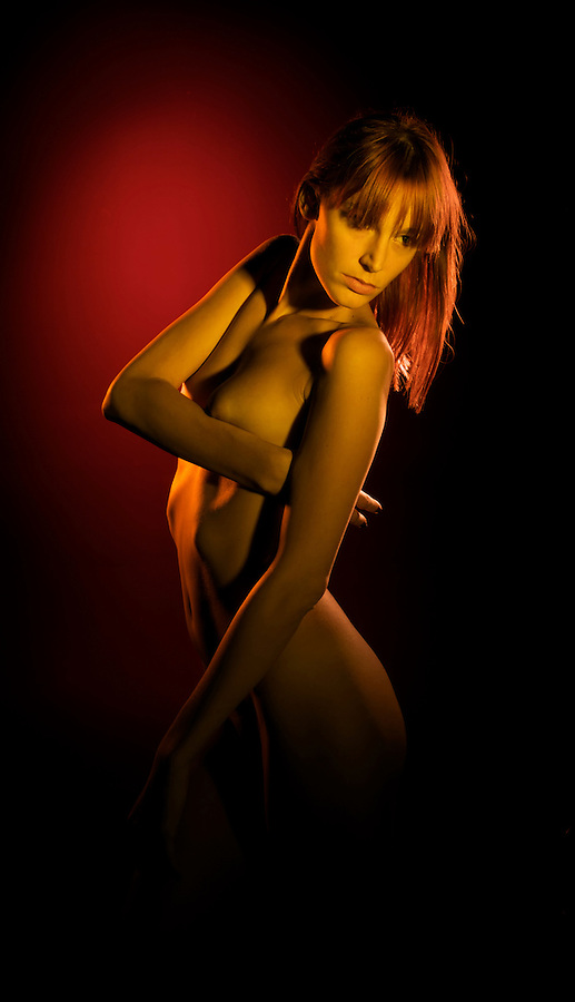 A young sensual woman poses nude under red light.z