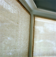 Natural linen blinds cover the bay window in this living room