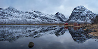 Boat sheds and mountains reflection on Selfjord in winter, Moskenesøy, Lofoten Islands, Norway