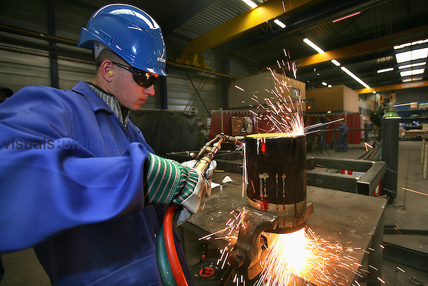Factory worker at a machinery plant welding metal pipes, Netherlands.