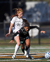 College of St Rose forward Laura Taylor (21) trips up Wilmington University midfielder Penelope Fantis (10).. In 2012 NCAA Division II Women's Soccer Championship Tournament First Round, College of St Rose (white) defeated Wilmington University (black), 3-0, on Ronald J. Abdow Field at American International College on November 9, 2012.