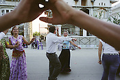 Tremura Balparno (centre of picture) dances with a male friend, as relatives and friends of the Badea family enjoy a party on the road outside their house, on the day of the baptism of grandson Sarion Bratu Badea. In the Roma camp of SIntesti, near Bucharest..