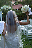 Bride walking away holding a bouquet of flowers in her raised hand