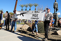 """Phoenix, Arizona. January 19, 2013 - Two men hold a banner during Saturday's rally in Phoenix to oppose to proposed changes in gun control laws. The sign reads: """"I will not comply,"""" in reference to Obama's gun control plans. As President Barack Obama proposed new gun regulations last week, gun owners demonstrated against it with national """"Guns Across America"""" rallies to defend the Second Amendment. Dozens showed up at the Arizona State Capitol, many of them carrying weapons. Photo by Eduardo Barraza © 2013"""