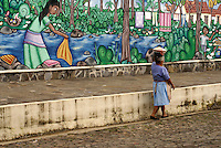 Woman carrying a basket on her head walking past a colourful mural in the village of Ataco in western El Salvador