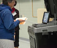 Fairfax, VA,November 8, 2016, USA:   Polling sites in Fairfax, VA are open and voters are making their voices heard in the 2016 Presidential elections. A woman places her ballot into the voting machine.  Patsy Lynch/MediaPunch