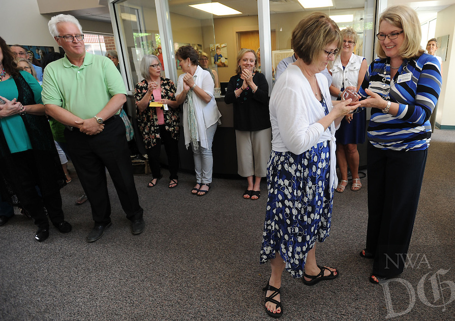 NWA Democrat-Gazette/ANDY SHUPE<br /> Retiring teacher Janice Ferguson (left) receives a gift of appreciation from Susan Heil, a member of the school board, Thursday, May 28, 2015, during a party to recognize those retiring from Fayetteville Public Schools at the district's administration office.