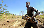 """A man makes bricks in a transition camp in war-torn northern Uganda. Two decades of war in northern Uganda have left almost two million people displaced, though progress in peace talks in 2006 initiated a small movement to return to home villages. Under a government-supervised return program, families are often required to spend several weeks in so-called """"satellite camps"""" before moving completely home."""
