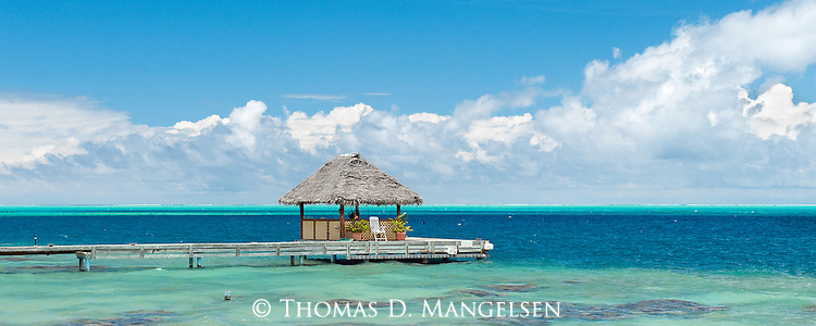 A thatched-roof cabana encompassed by a sea of turquoise and aquamarine is a tropical dream on Bora Bora in French Polynesia.