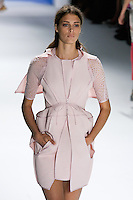 Claire de Regge walks runway in a rose super piqu6 sleeveless peplum coat with oversized hood and cutout pocket over rose silk chiffon eyelet dress.by Vera Wang, for the Vera Wang Spring 2012 collection, during Mercedes-Benz Fashion Week Spring 2012.
