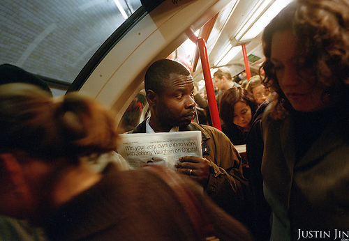 A man trying to read a newspaper is squashed at the gate of a London's Central Line metro during in rush hour..Picture taken 2005 by Justin Jin