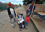 Tendai Nyamkondiwa accompanies her niece, Ngonidzashe Rondozai, as they visit with neighbors on the street where they live in Harare, Zimbabwe.  Rondozai, 17, has cerebral palsy, and Nyamkondiwa, her aunt, is her primary caregiver. Rondozai uses an appropriately designed and fitted wheelchair provided by the Jairos Jiri Association with support from CBM-US.