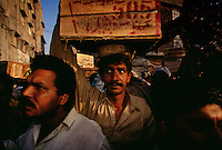 A busy morning near the market brings workers carrying goods to be sold.