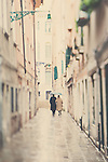 an older couple walk arm in arm along a venician street