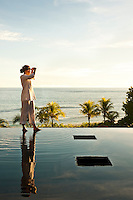A guest stands on the edge of the infinity pool admiring the view